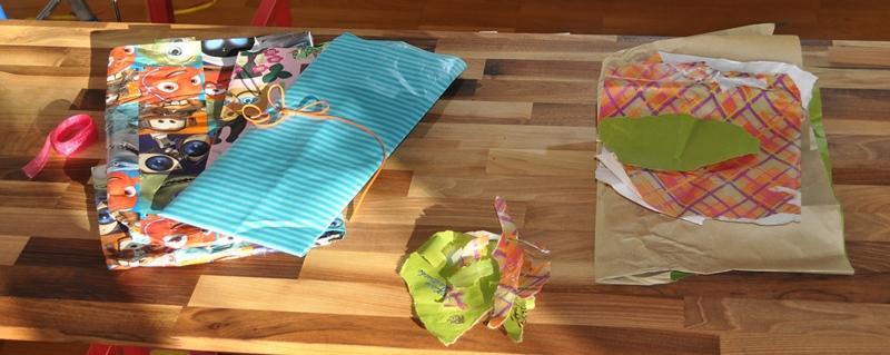 Geschenkpapier und Bänder (links) für Wiederverwendung, Abfall (Mitte), Altpapier (rechts)