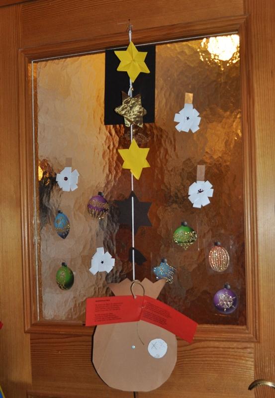 """Am 9.12.14 schmückten """"alte"""" von meinem Sohn gebastelte Sterne, von meiner Tochter im Kindergarten gebastelte Schneesterne und ein Samichlaussack und nun kugelige Verbindungen unsere Eingangstüre."""