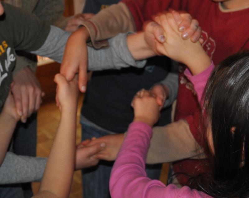 Jedes Kind hält mit je einer Hand ein andres Kind fest.