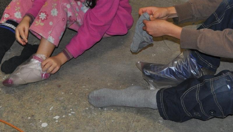 """Über die Socken ziehen die Kinder Plastiksäcke an und darüber """"alte"""" Socken. So können sie in Farbe treten."""