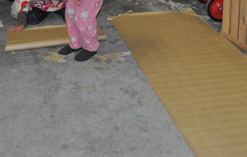 Warm angezogen, denn in unserer Werkstatt ist es kühl, helfen sich die Kinder gegenseitig, die Packpapierbahnen zu legen.