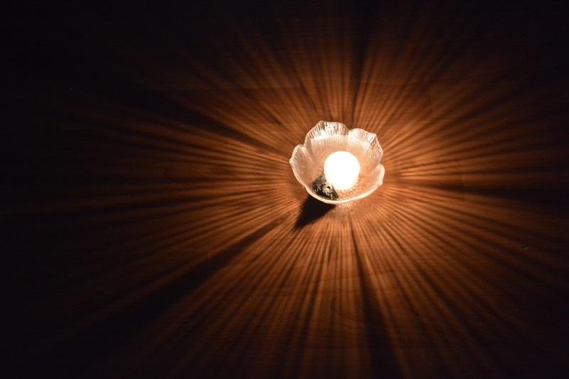 Der Stein liegt neben der brennenden Kerze. Wenn die Kerzen erloschen sind, kommt der Stein aufs Fensterbrett oder auf den Türrahmen.