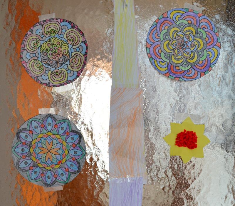 Unsere Eingangstür ist geschmückt mir Frühlingsmandalas und Häkelanschlagblume meines Sohnes und Frühlingsfarbenstreifen meiner Tochter.