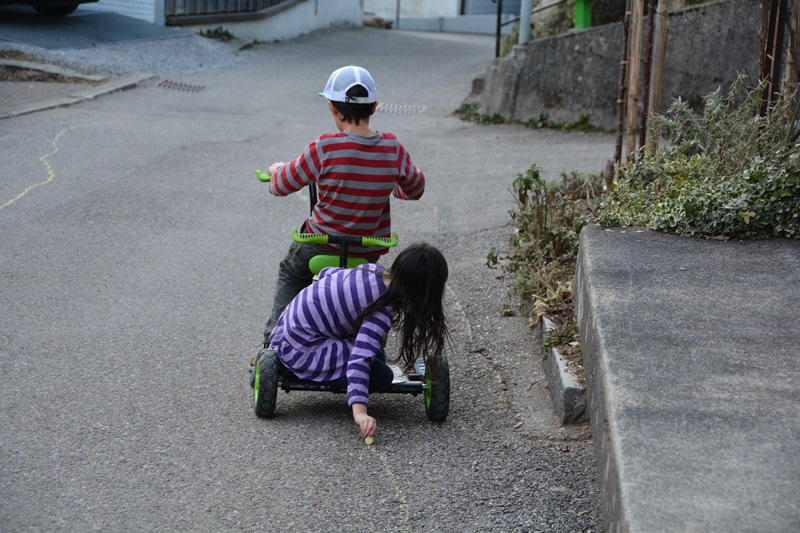 Mit dem Fahrzeug aus der Ludothek malen die Kinder eine Strasse auf die Strasse. Meine Tochter hält die Kreide auf den Boden während mein Sohn fährt.